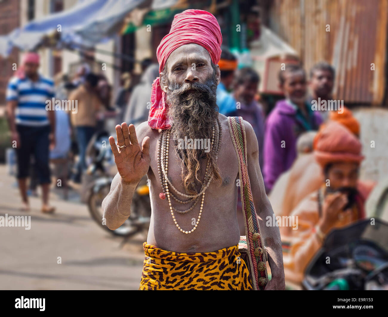 Portrait of a sadhu (Indian holy man) covered in ash and wearing brightly colored attire on a busy street in Varanasi, - Stock Image