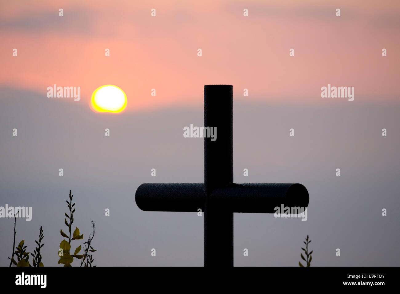 Rocca Ripesena, Umbria, Italy. Clifftop memorial cross silhouetted against the rising sun. - Stock Image