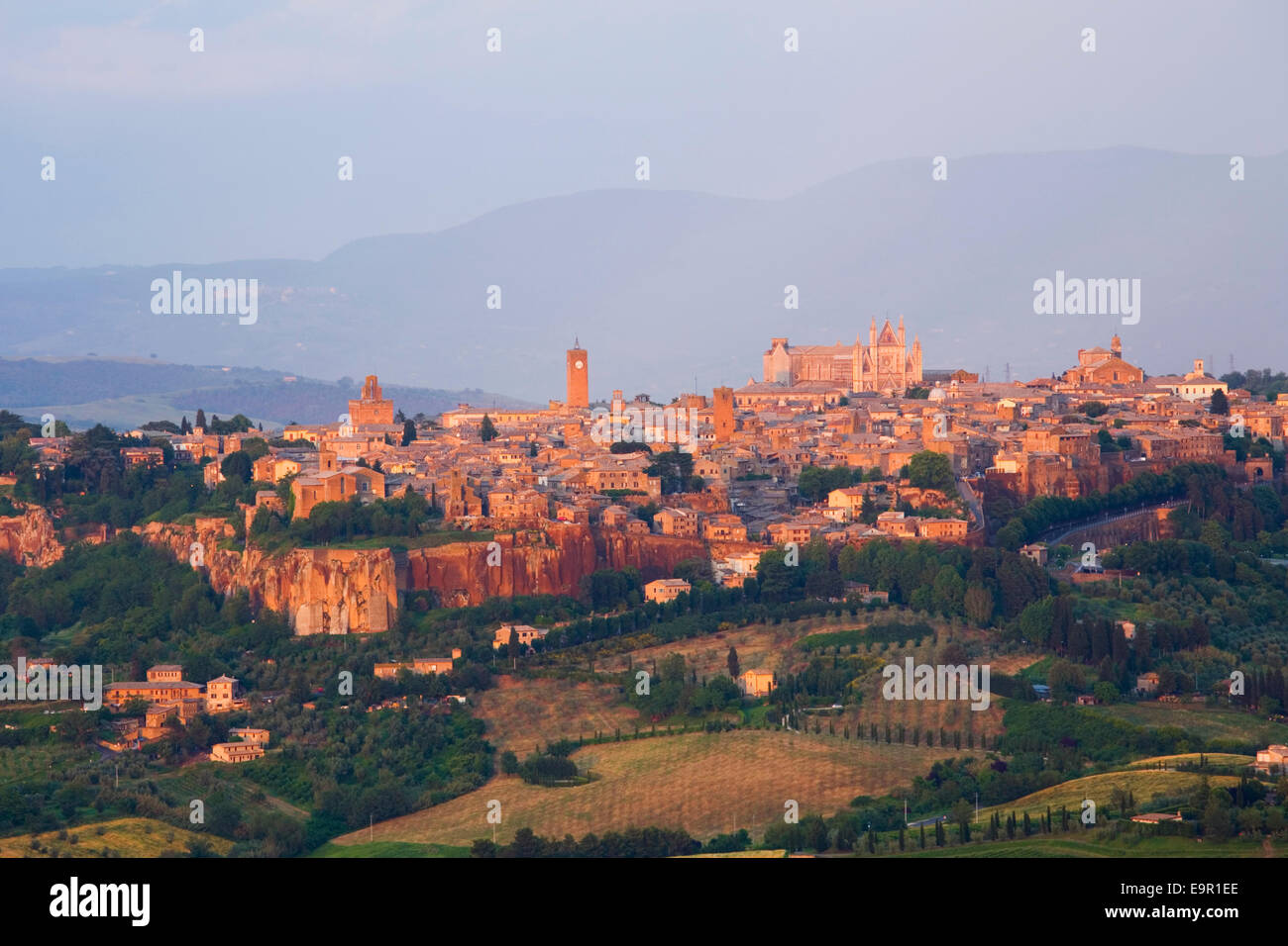 Orvieto, Umbria, Italy. View to the city skyline across agricultural landscape, sunset. Stock Photo