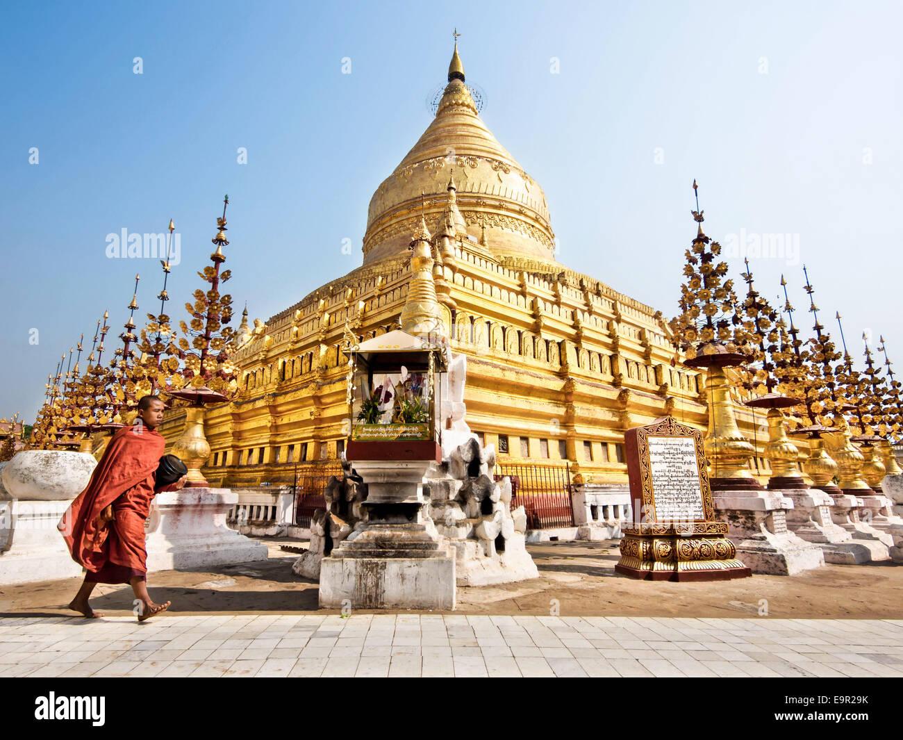 A Buddhist monk walking around sacred Shwezigon Paya, one of Myanmar's most revered pagodas, in Bagan, Myanmar - Stock Image