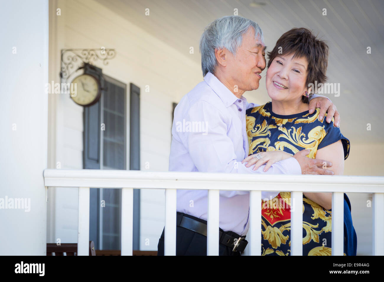Attractive Happy Chinese Couple Enjoying Their House Outside. - Stock Image