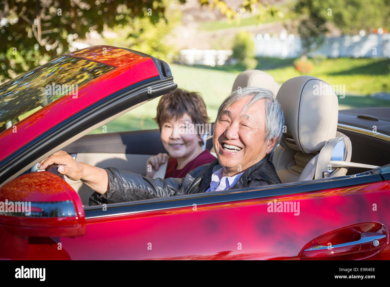 Attractive Happy Chinese Couple Enjoying An Afternoon Drive in Their Convertible. - Stock Image