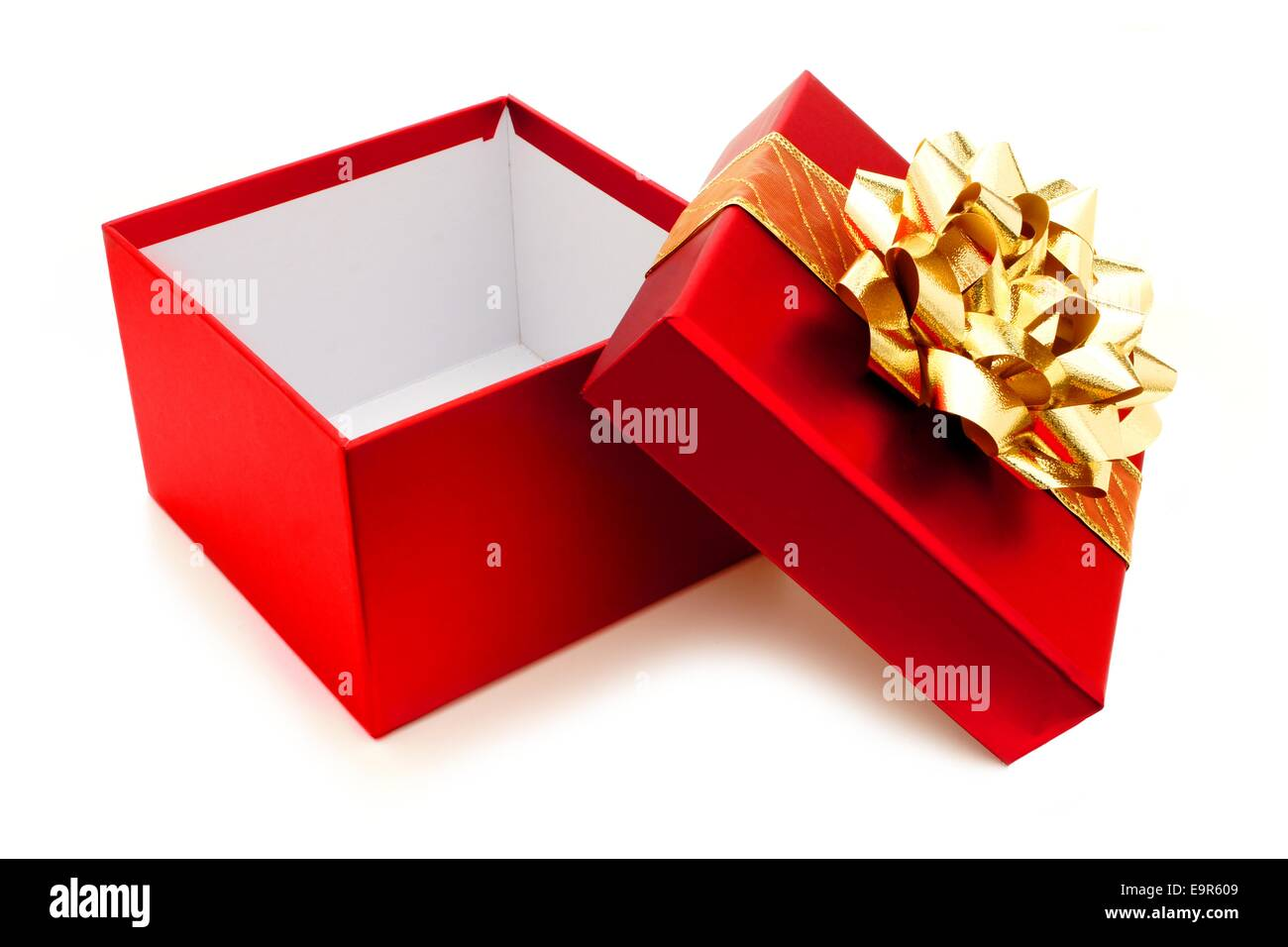 Opened red Christmas gift box with gold bow and ribbon Stock Photo