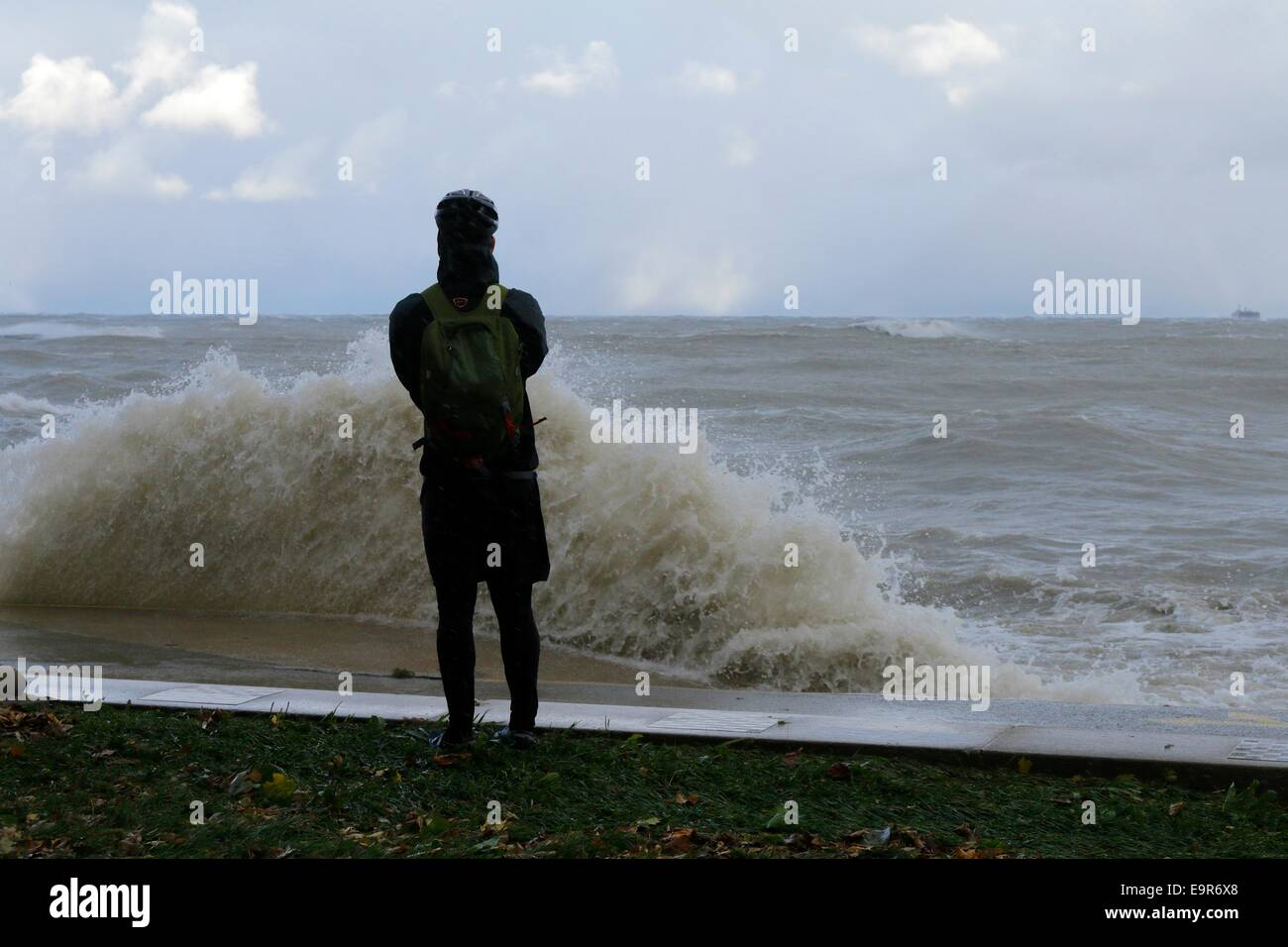 Chicago, Illinois, USA. 31st October, 2014.  A photographer takes shots of raging Lake Michigan during today's gale. Stock Photo