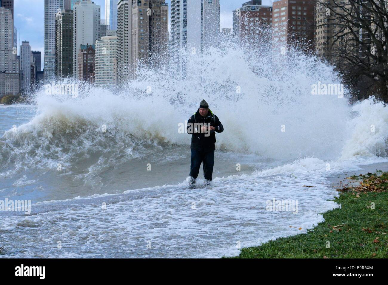 Chicago, Illinois, USA. 31st October, 2014.  A large Lake Michigan wave soaks a photographer who got a bit too close Stock Photo