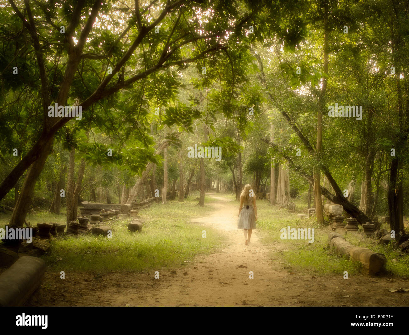 Young woman walking on a mysterious path into an enchanted forest. - Stock Image