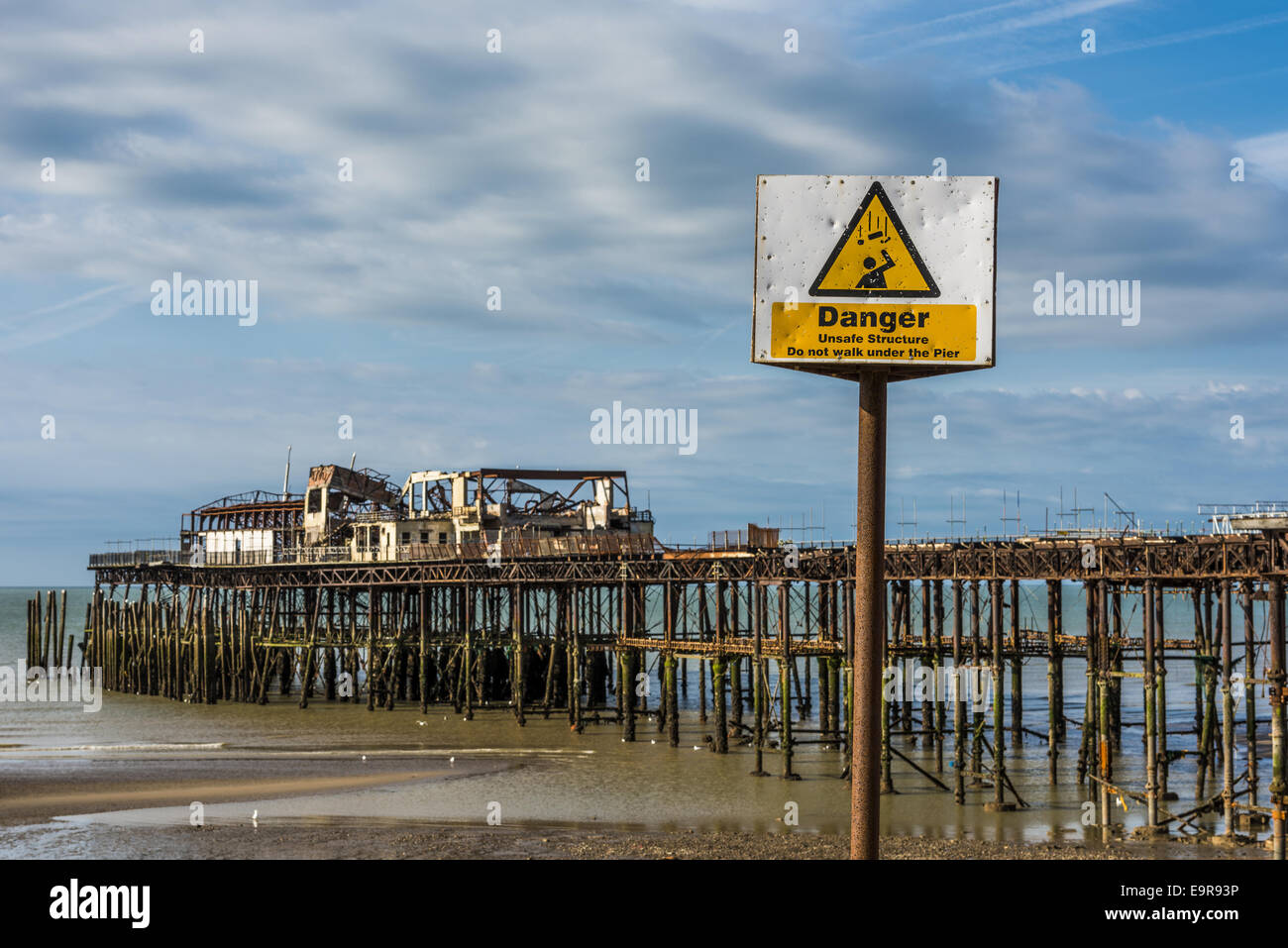 Danger, unsafe structure reads the sign following a fire at the Pier in Hastings, a popular seaside town in East - Stock Image