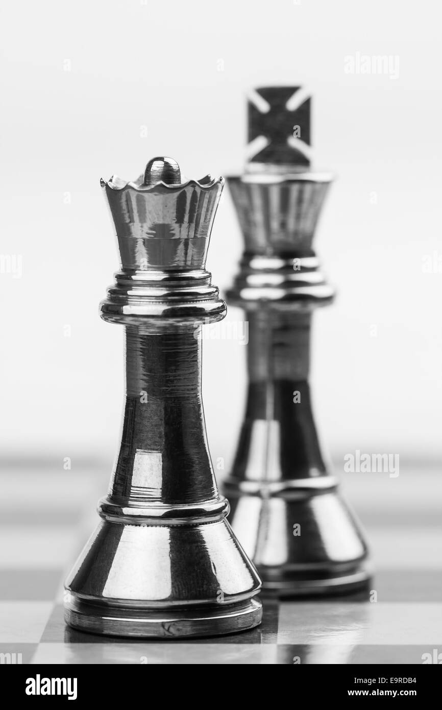 Rugged brass chess queen and king pieces on a chess board. Shallow DOF used for emphasis of powerful queen. - Stock Image