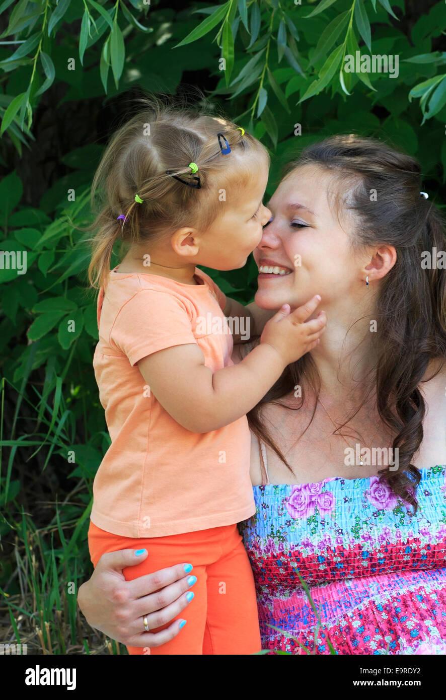 Little girl tenderly kisses and hugs mother. - Stock Image