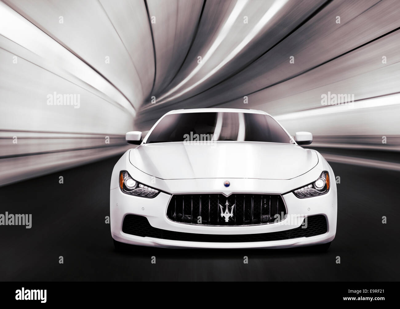 White 2014 Maserati Ghibli S Q4 luxury car speeding in a tunnel. Front view. - Stock Image