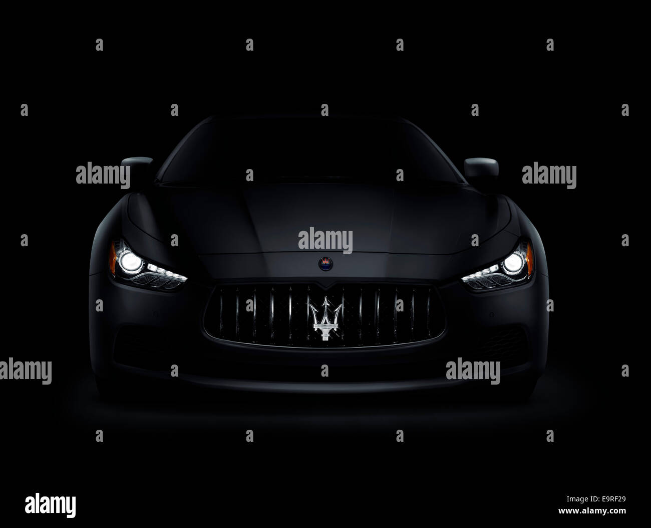 Dramatic photo of a dark 2014 Maserati Ghibli S Q4 luxury car front view with shining headlights isolated on black - Stock Image