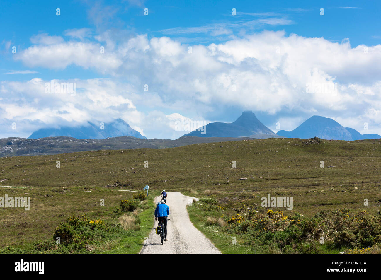 Tourists cycling by Stac Pollaidh - Stack Polly - (centre) in glacier mountain range in the North West Highlands - Stock Image