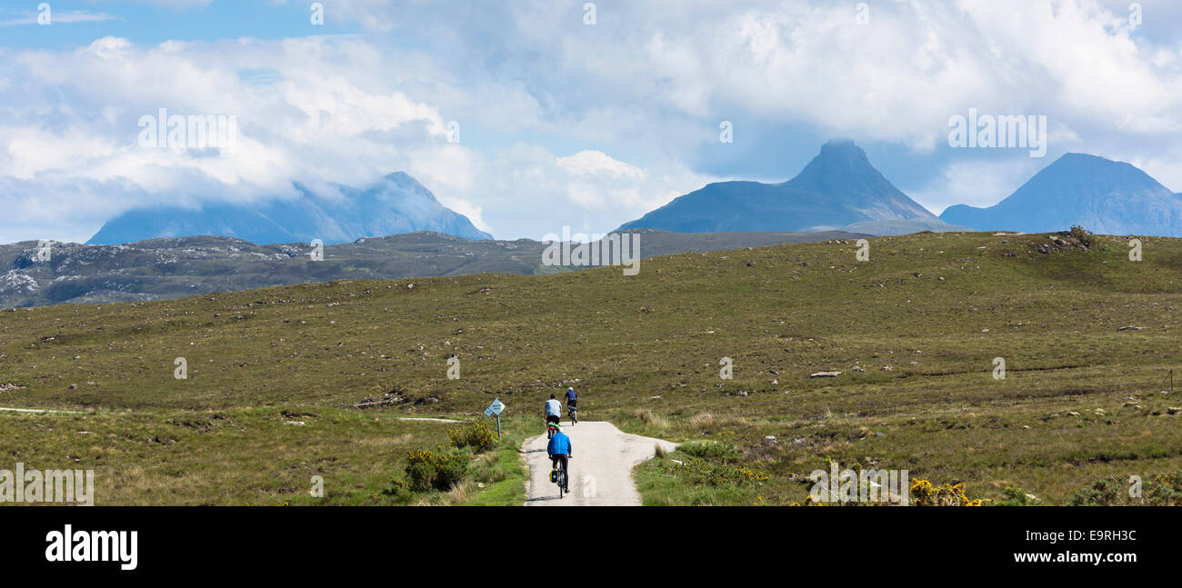 Tourists cycling by Stac Pollaidh - Stack Polly - in glacier mountain range in the North West Highlands Geopark - Stock Image