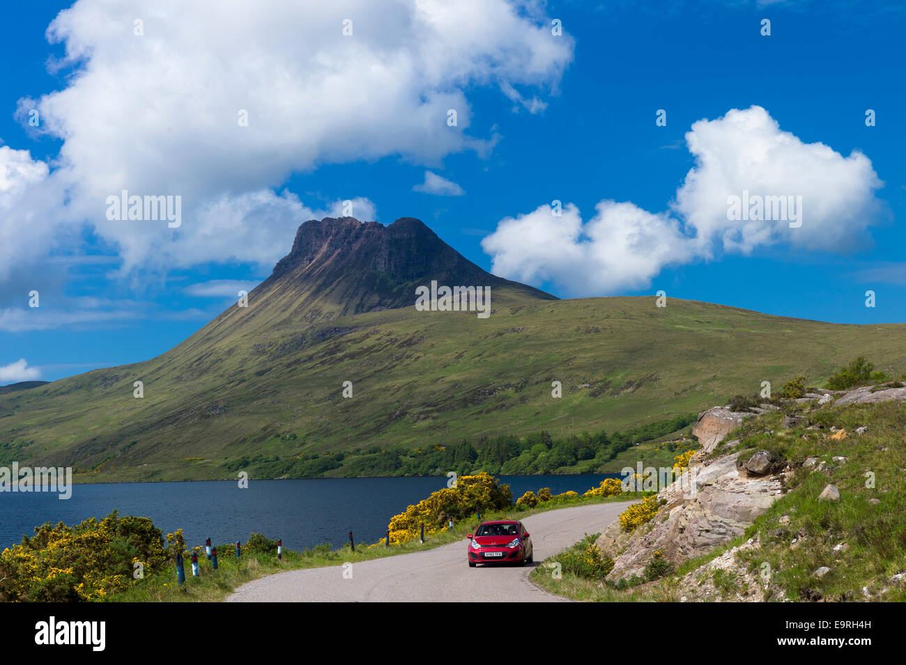 Motorist on touring holiday passes Stac Pollaidh, Stack Polly, mountain, within Inverpolly National Nature Reserve - Stock Image