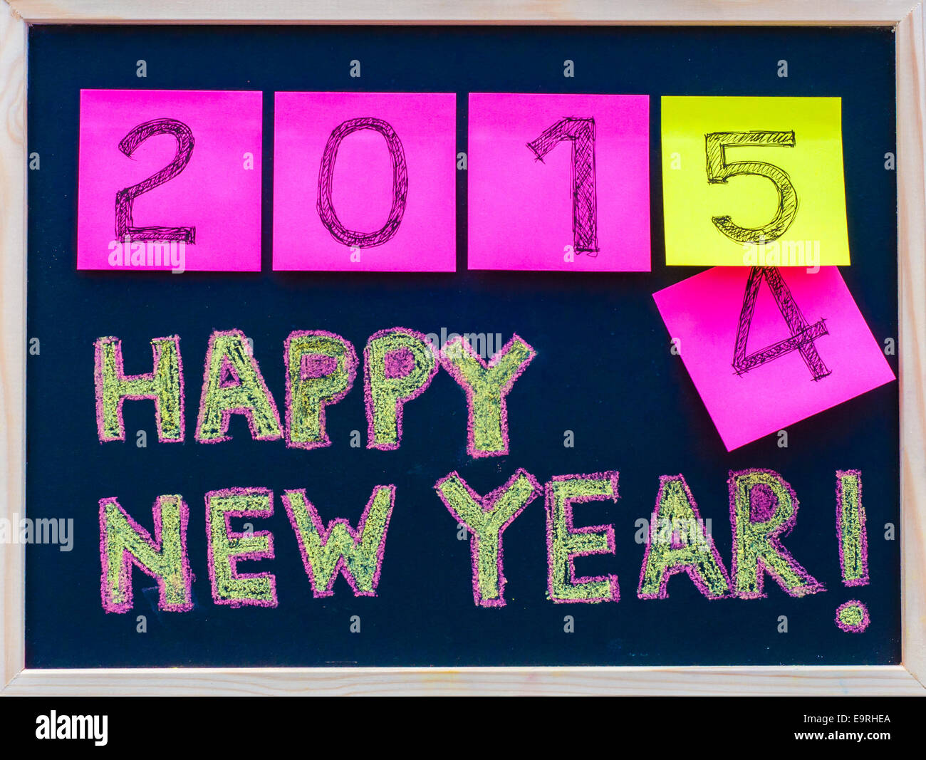Happy New Year 2015 message hand written on blackboard, numbers stated on post-it notes, 2015 replacing 2014 - Stock Image