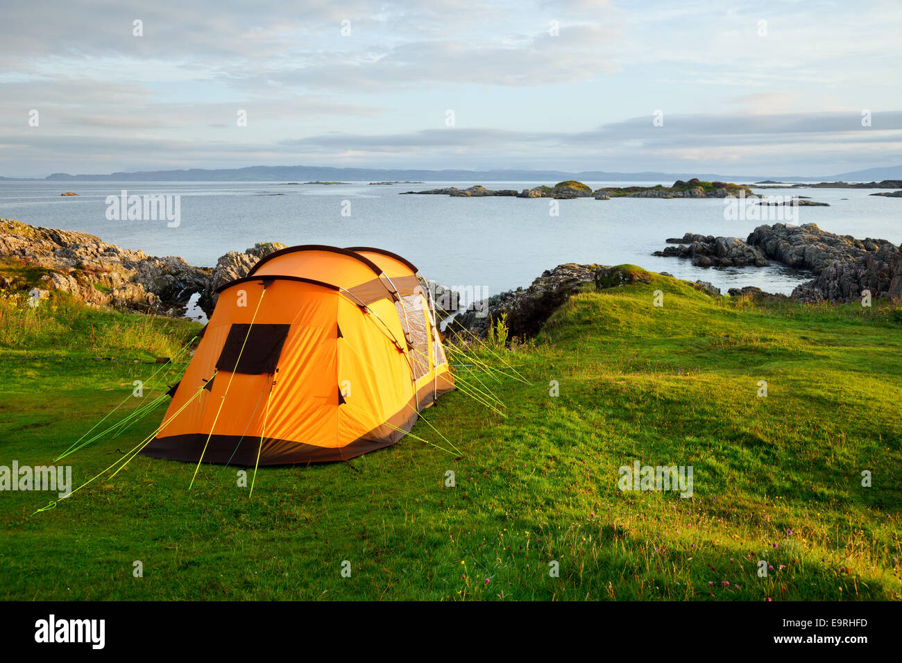 Orange camping tent on a shore in a morning light - Stock Image