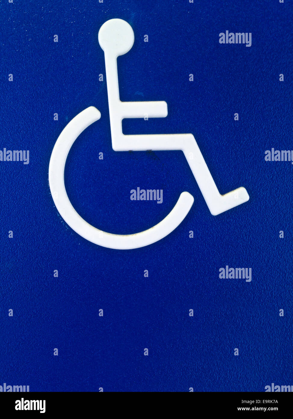 Disability person symbol on blue metal sheet - Stock Image