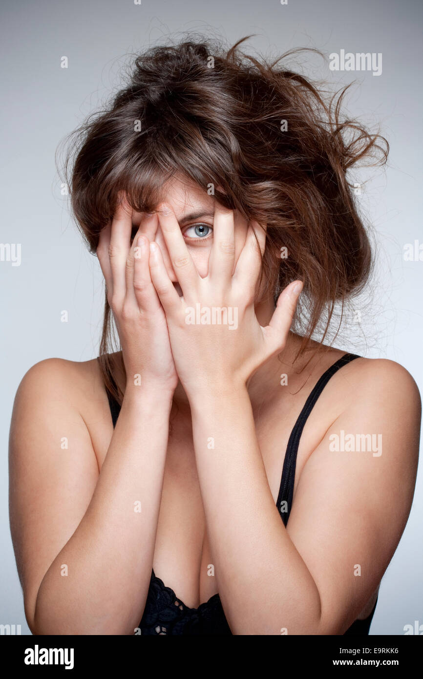 Woman Covering Face with Hand, Looking with One Eye through Fingers - Stock Image