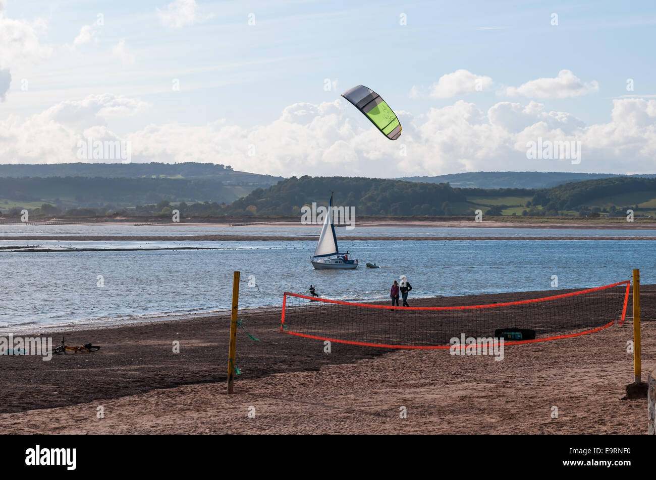 A kite surfer on a windy day at the river Exe estuary with beach walkers, a sail boat and a volley ball net in the - Stock Image