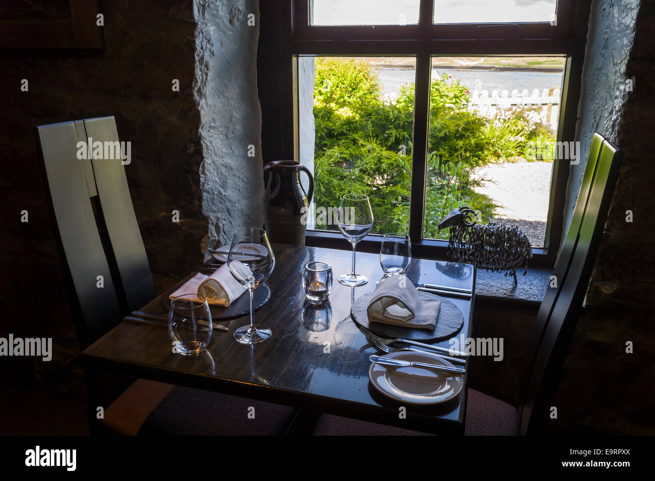 Table place setting with glassware, crockery, cutler, and napkins at renowned gastronomic five star restaurant The - Stock Image