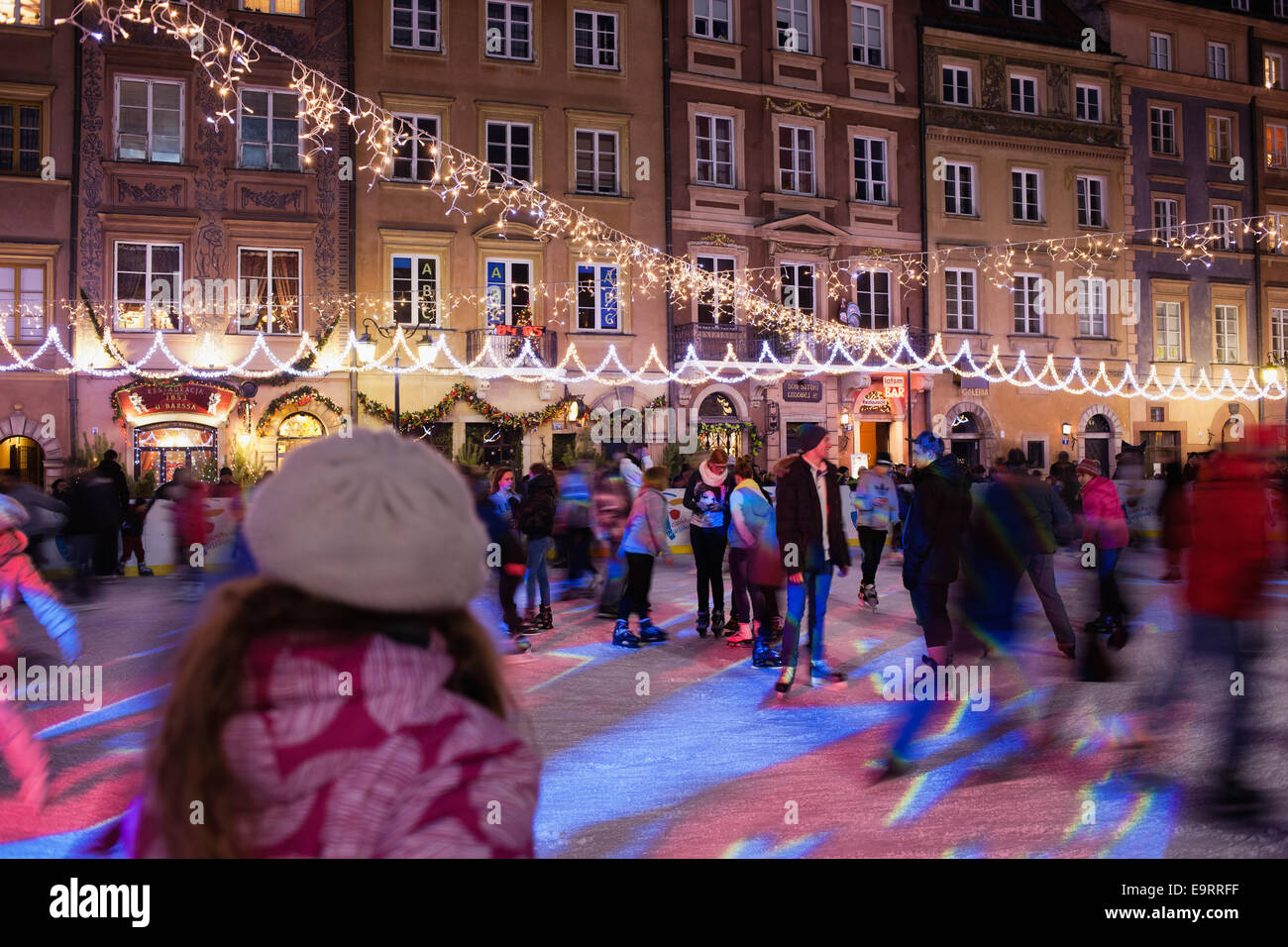 People skating on ice rink during Christmas Time in the Old Town Square of Warsaw, Poland. - Stock Image