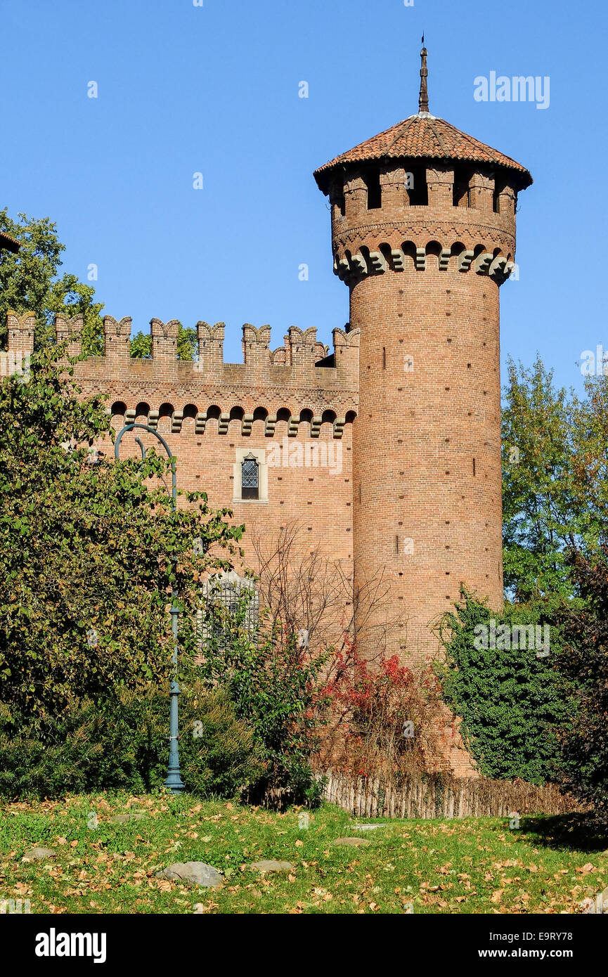 The tower of the medieval castle in the Valentino Park, Turin (Italy), surrounded by vegetation with the background Stock Photo