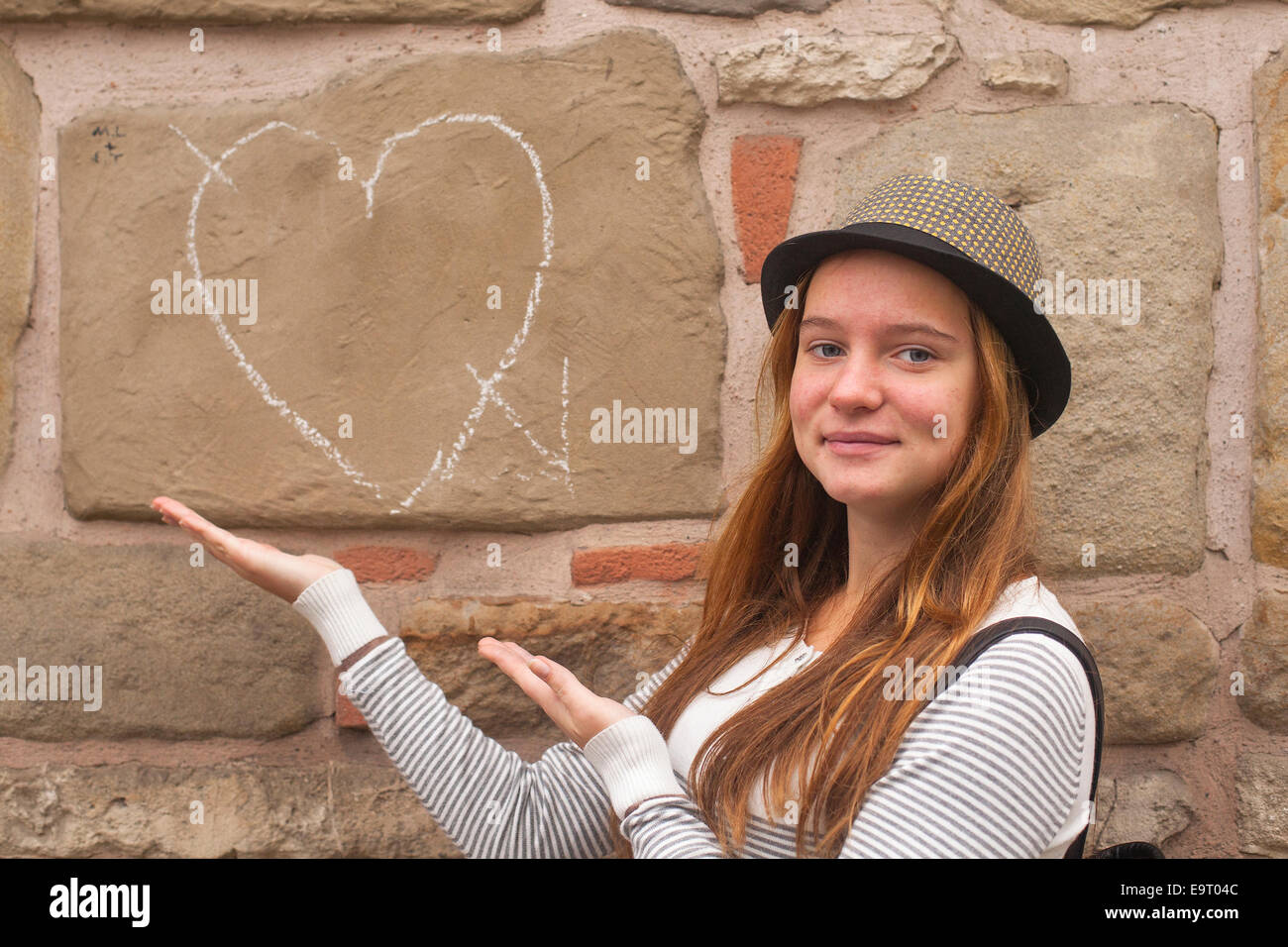 Cute young girl near a wall painted chalk heart and arrow. Falling in love concept. Stock Photo