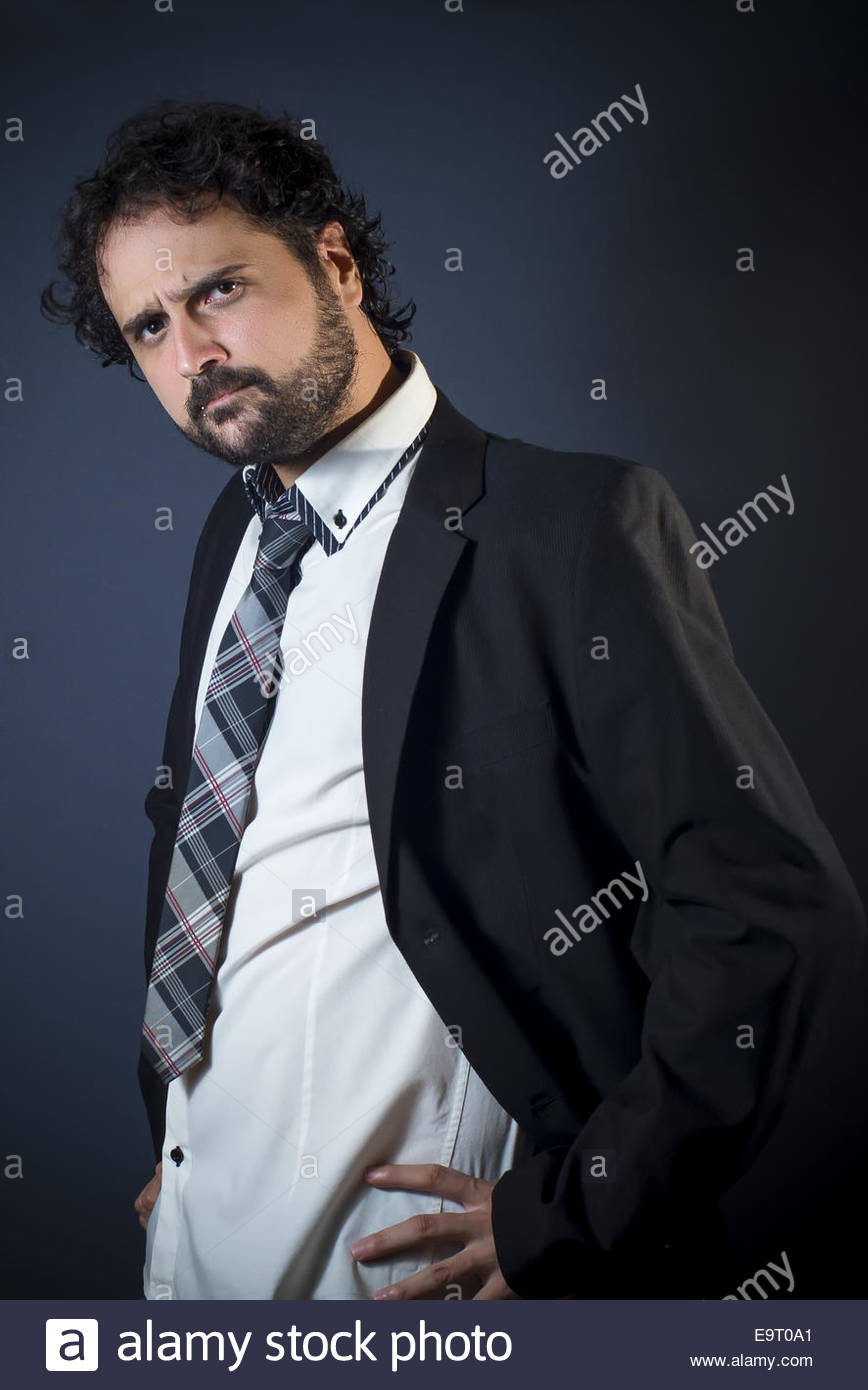 Portrait of young man with jacket, expression suspicious. - Stock Image