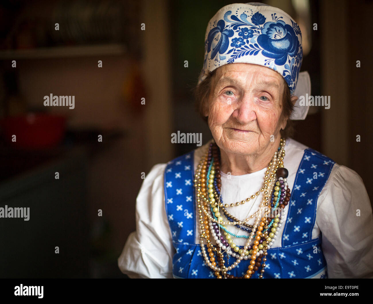 Portrait of Slavic grandmother in traditional clothes indoors. - Stock Image
