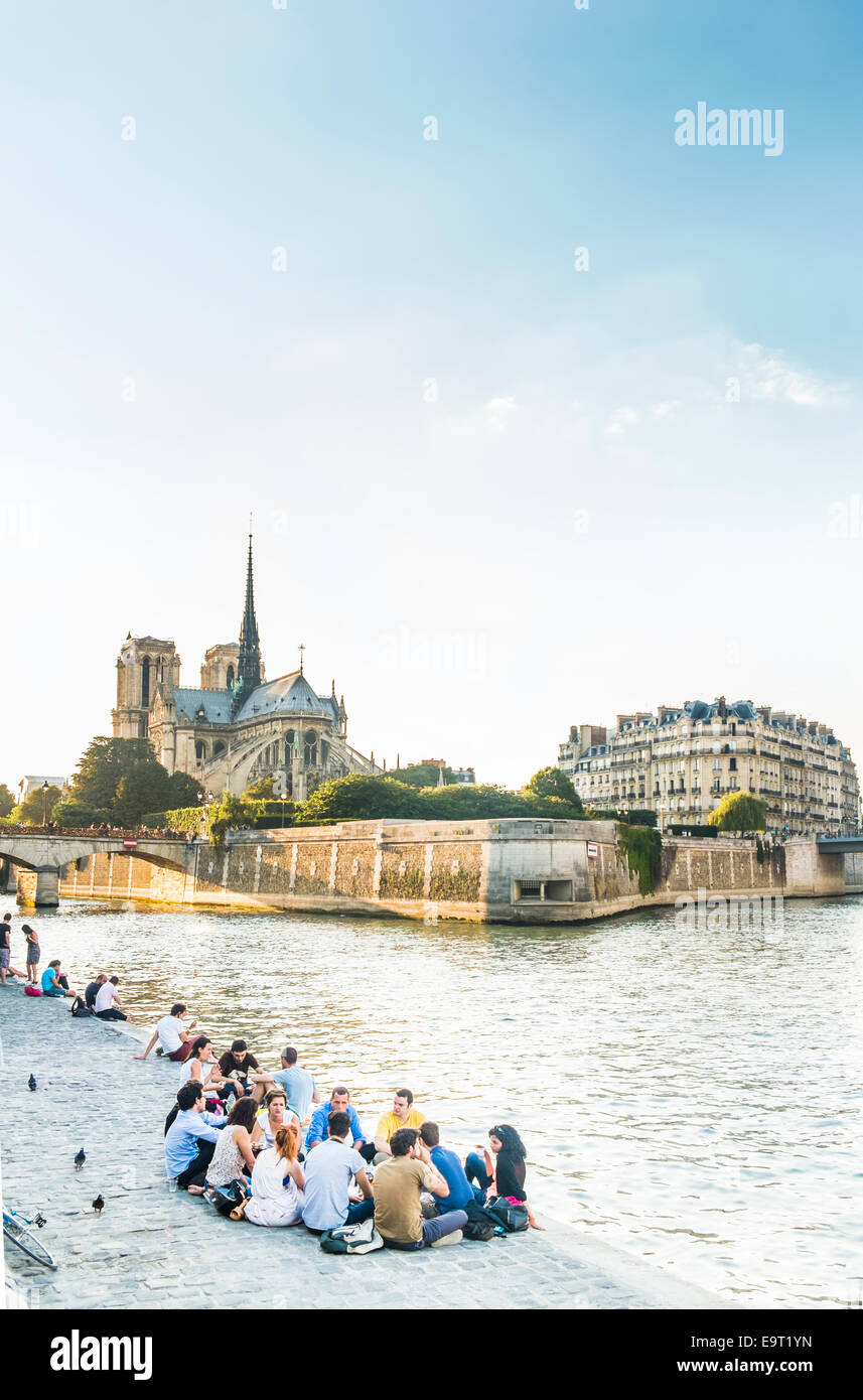 young people are having a picnic in the early evening on the banks of river seine, in the background ile de la cité - Stock Image