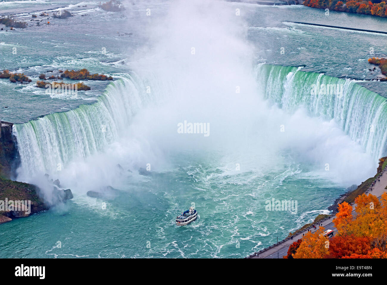 Niagara Falls with tour boat Maid of The Mist in Niagara River and WEGO Bus on Niagara Parkway. - Stock Image