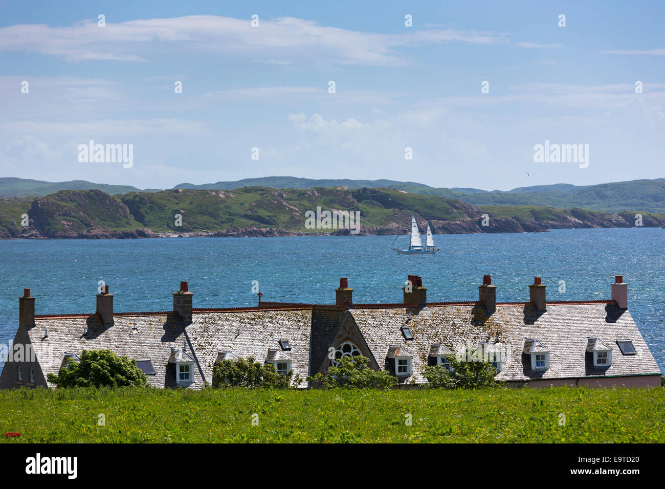 Sailboat passing rooftops of homes on Isle of Iona in the Inner Hebrides and Western Isles, West Coast of SCOTLAND - Stock Image
