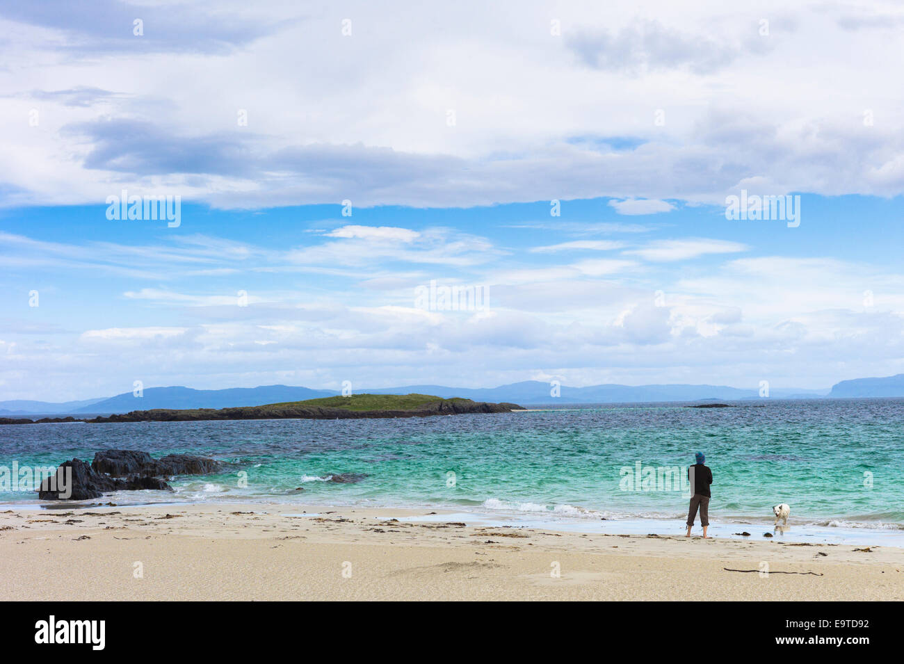 Lone person with dog on shoreline of sandy beach looking out to turquoise sea on Isle of Iona in the Inner Hebrides Stock Photo