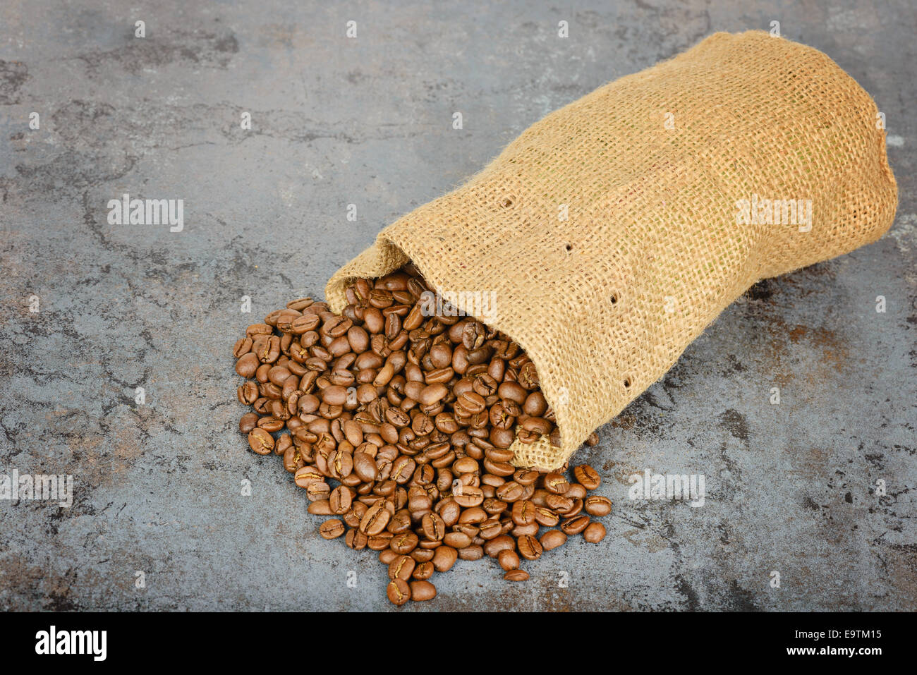 Coffee beans spilled out of the bag - Stock Image
