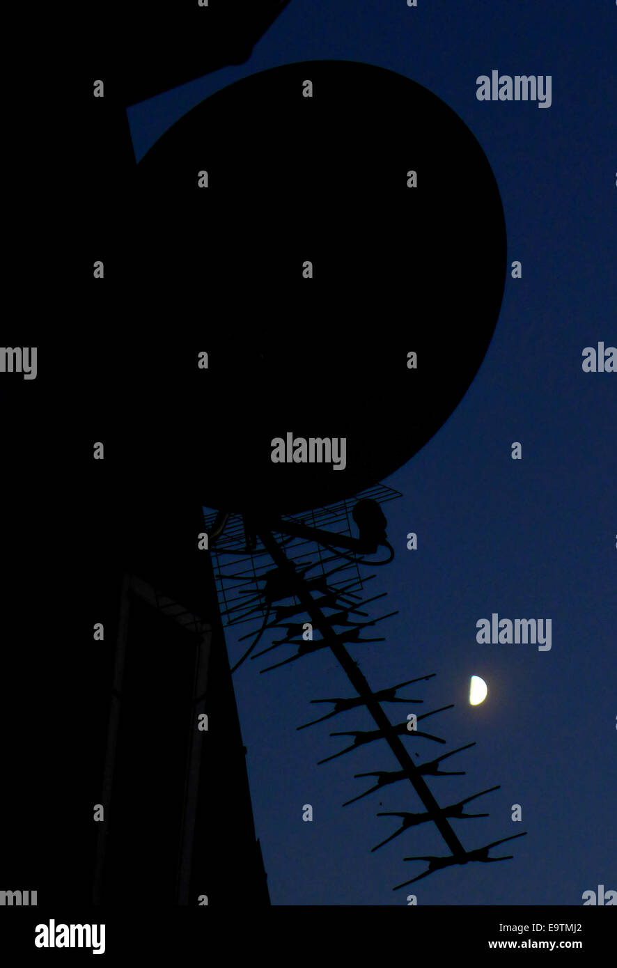 Aerial and satelitte dish silhouetted against a moonlit sky. - Stock Image