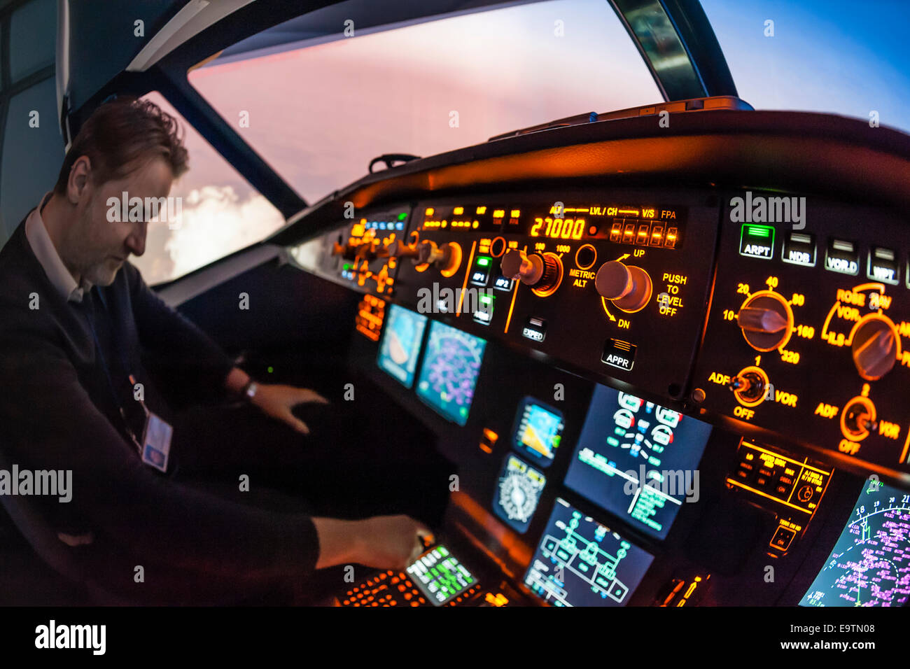 Cockpit of an Airbus A320 flight simulator that is used for training of professional airline pilots (pilot adjusting - Stock Image