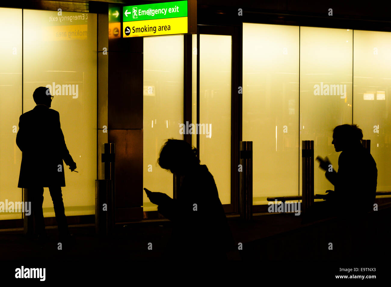 Three smokers in smoking area outside building at night. - Stock Image