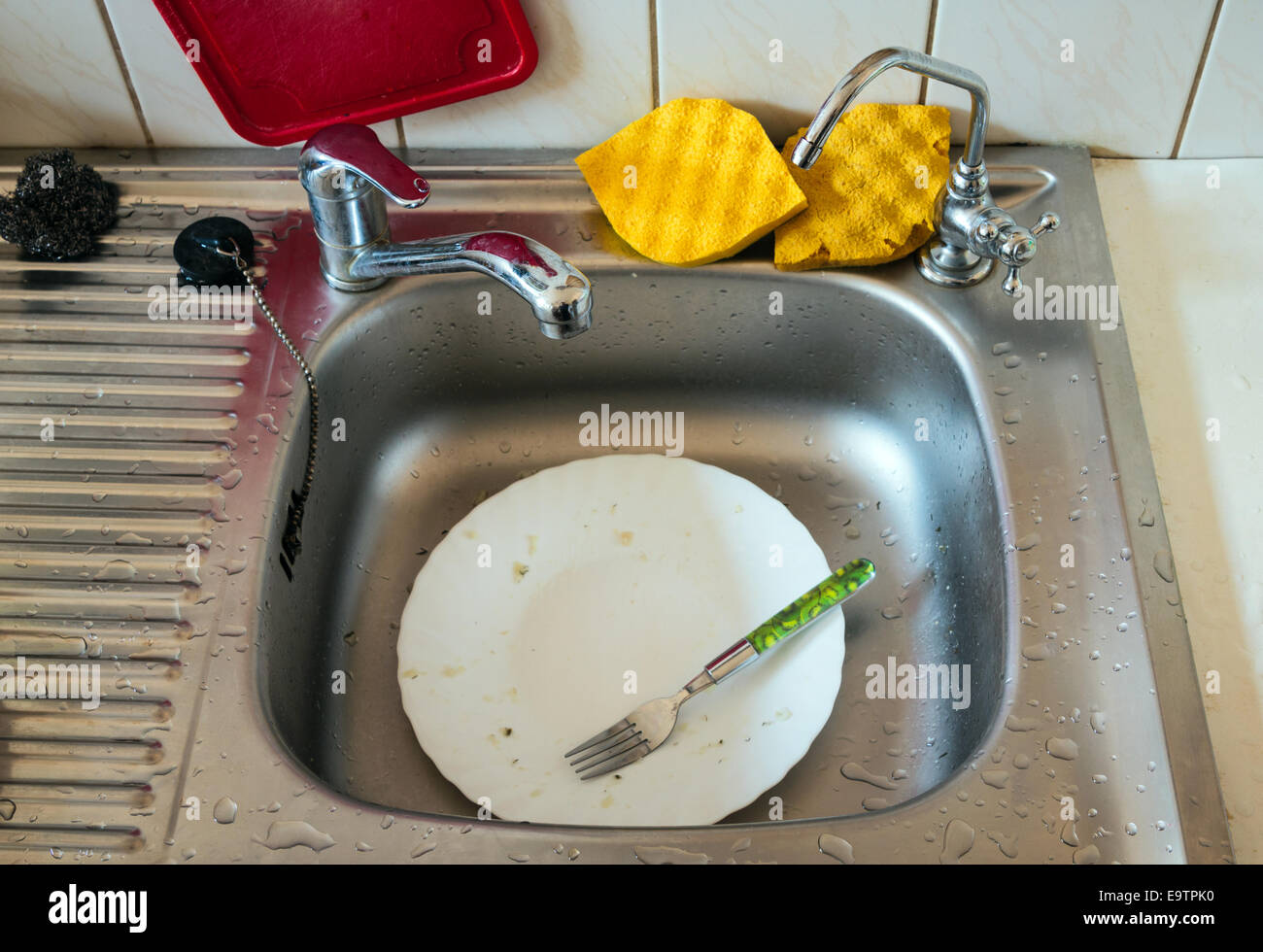 Unwashed dish in kitchen sink - Stock Image