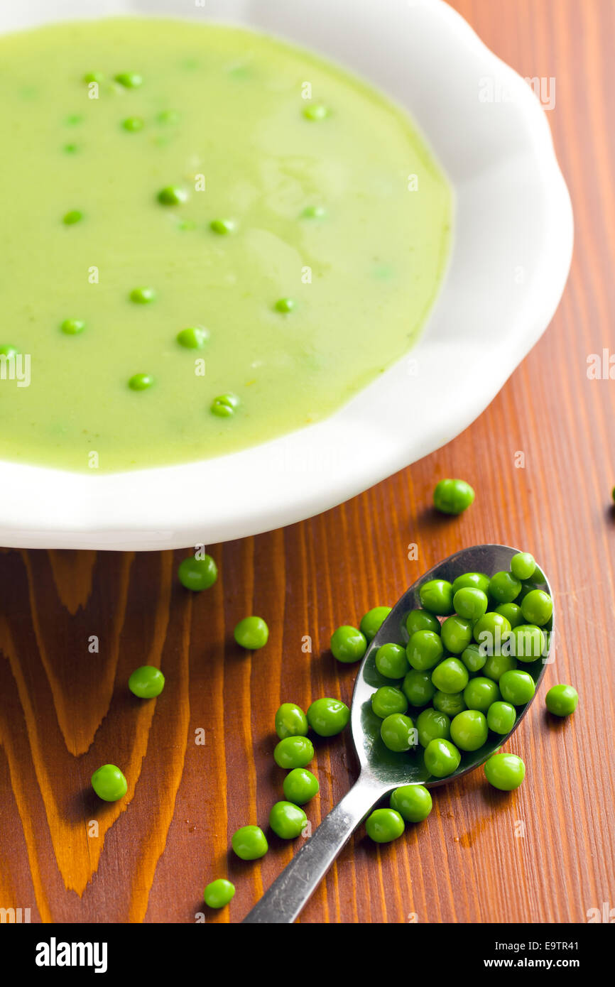 pea soup in plate on kitchen table - Stock Image