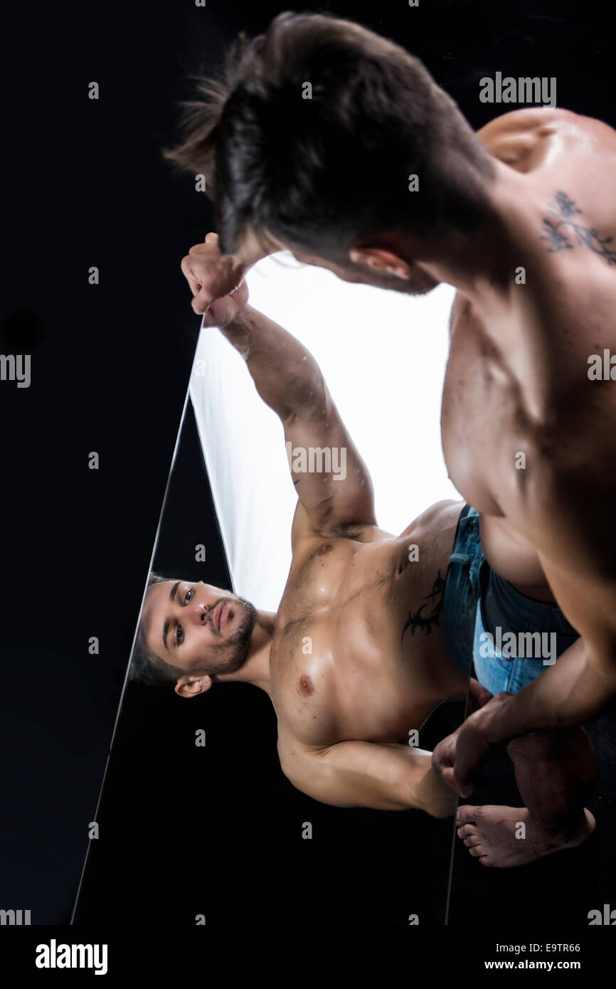 Narcissistic handsome shirtless young man admiring his reflection in the mirror in a show of self-absorption - Stock Image
