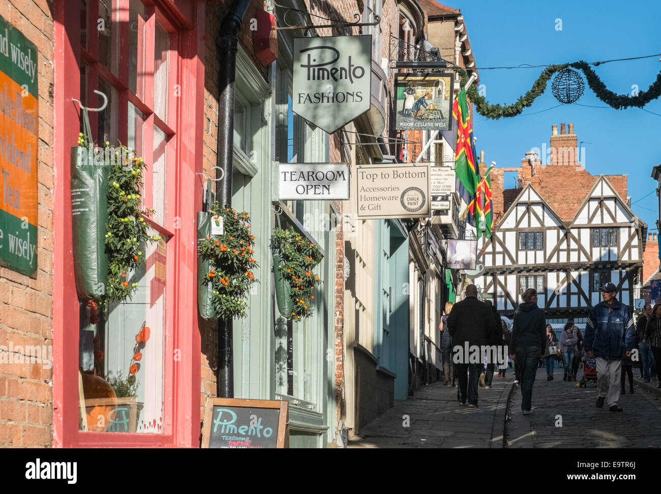 Shop fronts and shoppers on Steep Hill, Lincoln, Lincolnshire, UK - Stock Image