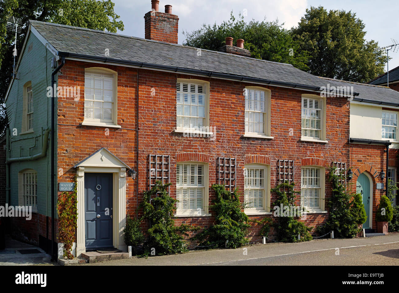 Terraced red brick houses in Cavendish Suffolk England - Stock Image