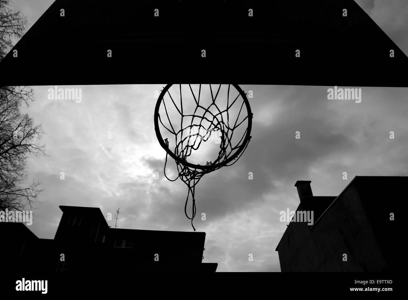 A silhouette of a basketball hoop at playground, taken from below - Stock Image
