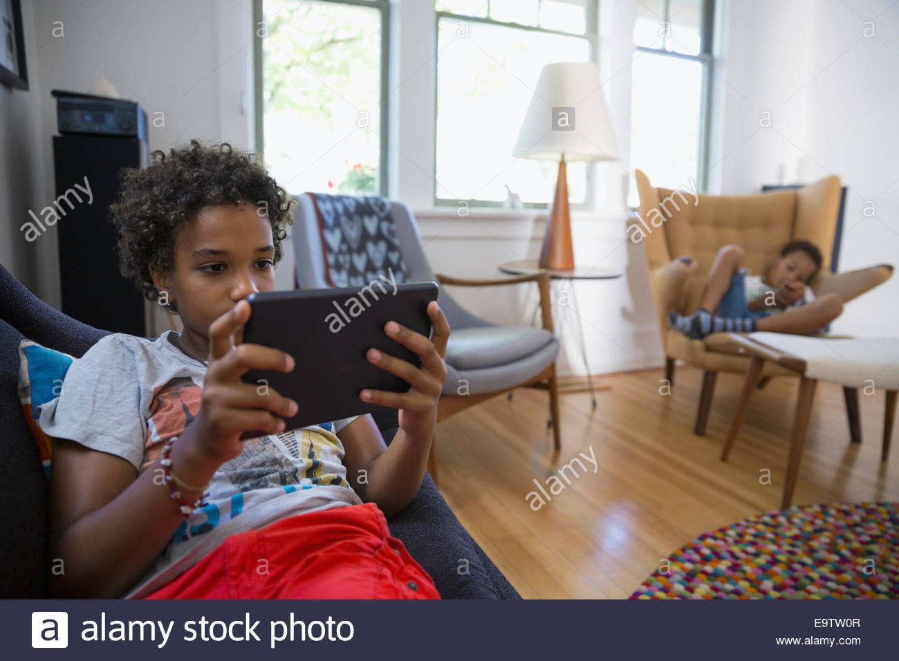 Brothers using technology in living room - Stock Image