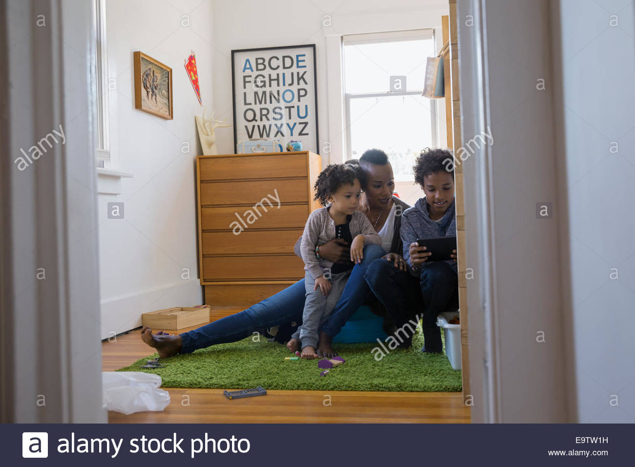 Mother and children using digital tablet in bedroom - Stock Image