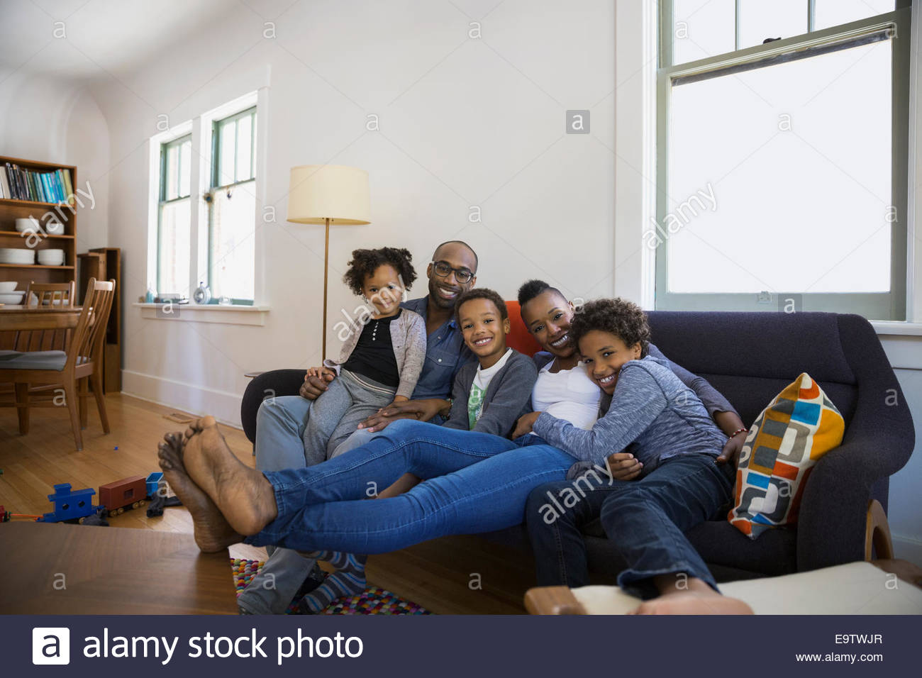 Portrait of smiling family on living room sofa - Stock Image