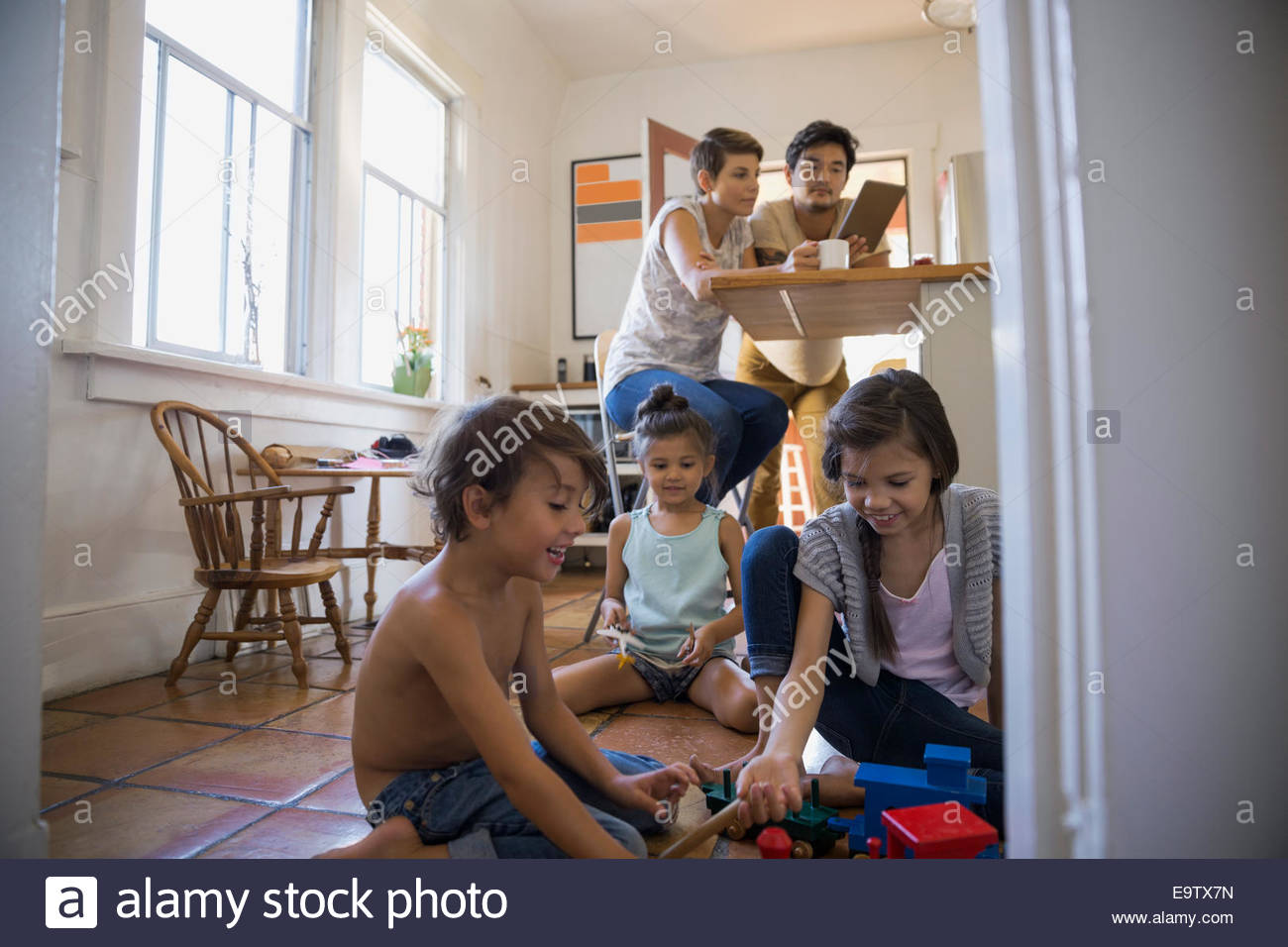 Children playing on kitchen floor Stock Photo