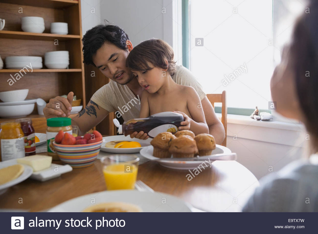 Father watching son pour syrup on pancakes - Stock Image