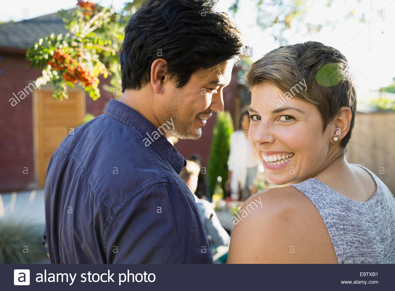 Portrait of smiling couple in backyard - Stock Image