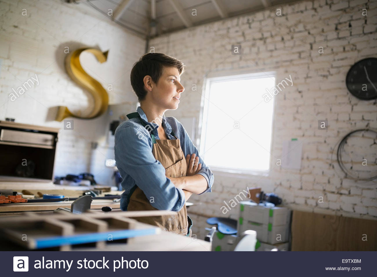 Pensive female carpenter with arms crossed in workshop - Stock Image